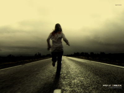 Poster for the Australian horror movie Wolf Creek: girl running away on road, filmed from behind