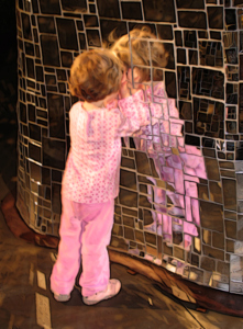 little girl in pink clothes explores herself in large kaleidoscopic mirror