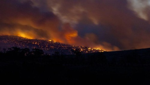 hills at night glowing with bushfires, sky covered in orange-grey smoke clouds